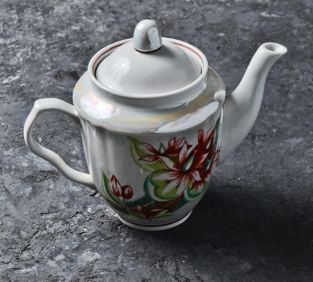 Un antico teiera in ceramica close-up con motivi su un tavolo di cemento nero.