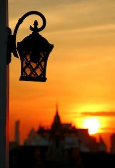 Lampada antica con silhouette sfocata di un tempio all'alba a bangkok
