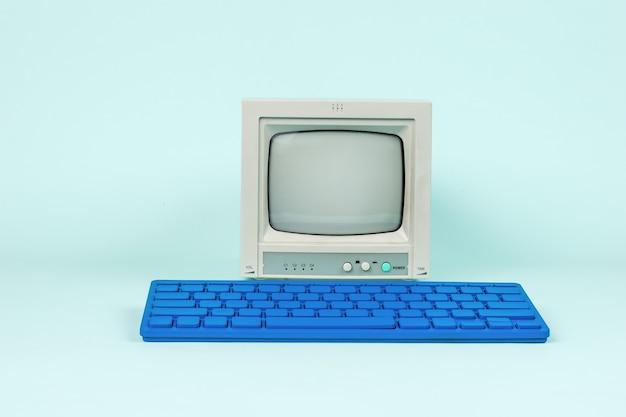 Un monitor antico e un'elegante tastiera blu su sfondo azzurro.