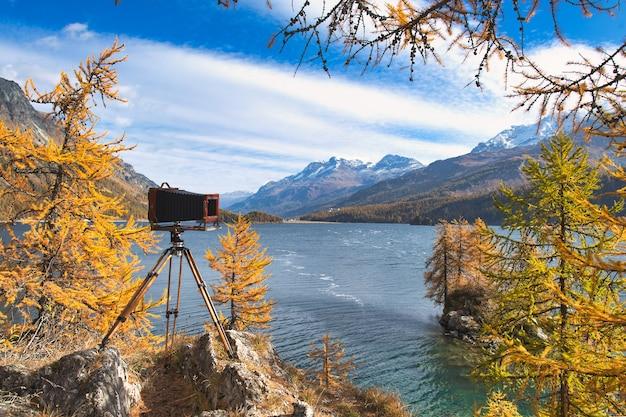 Macchina fotografica antica del piatto su treppiede di legno durante una foto di paesaggio