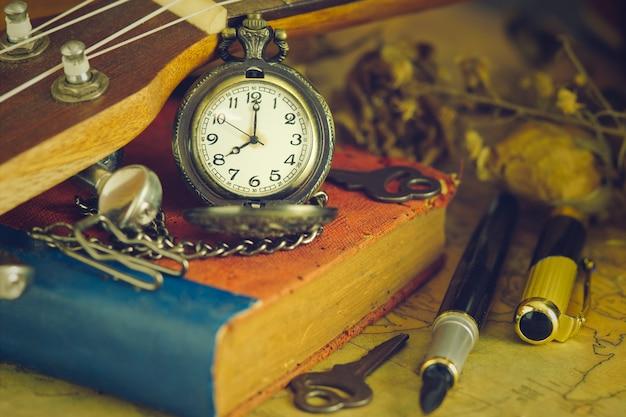 Un antico orologio da tasca appoggiato a un ukulele e un vecchio libro con mappa vintage