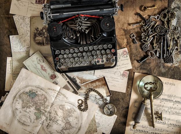 Macchina da scrivere antica e accessori per ufficio vintage sul tavolo di legno. natura morta nostalgica