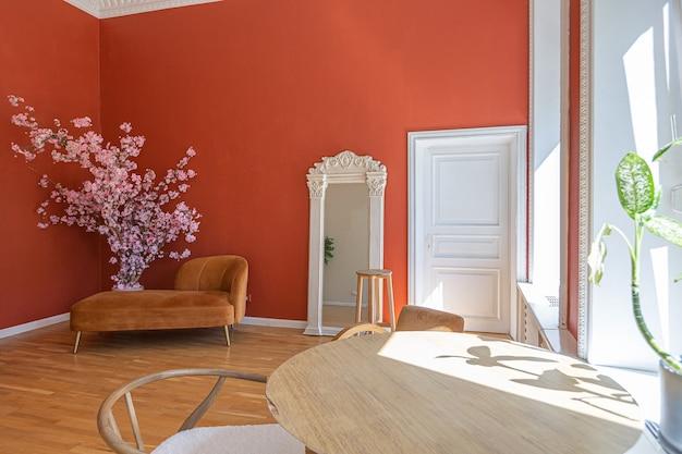 Interni d'epoca d'epoca in soggiorno in stile ottocentesco con pareti rosse luminose, pavimento in legno e luce solare diretta all'interno della stanza.