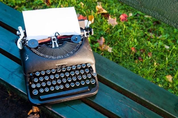 Antica macchina da scrivere vintage su sfondo autunnale con foglie cadute sulla panchina