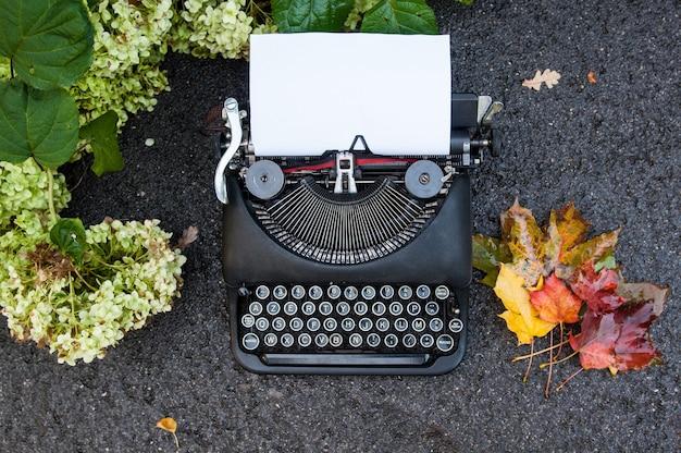 Antica macchina da scrivere vintage su sfondo autunnale con foglie cadute