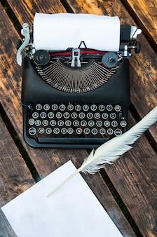 Antica macchina da scrivere vintage su un tavolo di legno, penna e foglio di carta