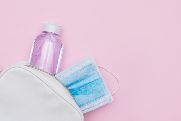 Maschera di protezione antisettica e sterile di protezione in borsa bianca sulla tavola rosa con uno spazio della copia.