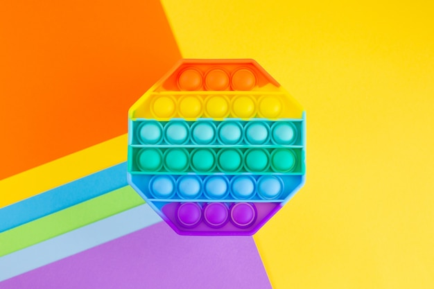 Antistress pop it toy arcobaleno sensoriale in silicone su sfondo colorato