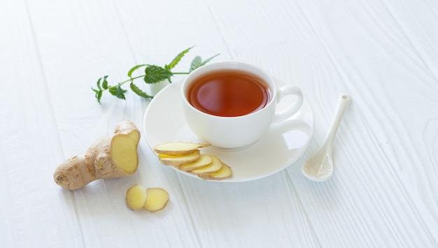 Bevanda antivirale. tè ayurvedico sano con zenzero e foglie di menta in tazza bianca