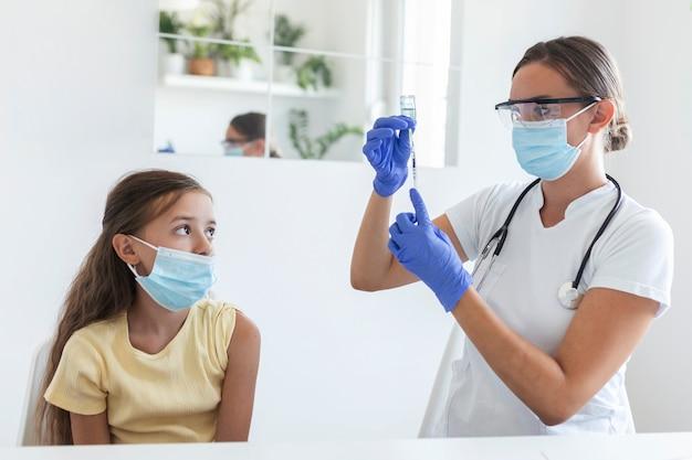 Concetto di campagna di immunizzazione antivirale. ragazza di vaccinazione del medico. ragazza in maschere mediche che viene vaccinata contro il covid-19, medico che fa iniezione di vaccino contro il coronavirus in ospedale.
