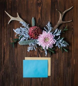 Corna decorate con fiori vicino a buste su legno