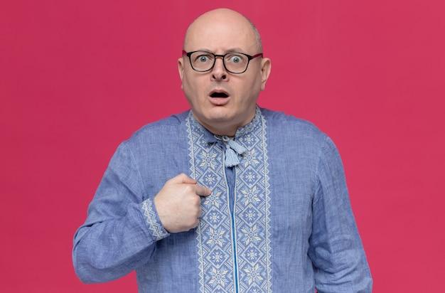 Uomo adulto ansioso in camicia blu con gli occhiali che punta a se stesso