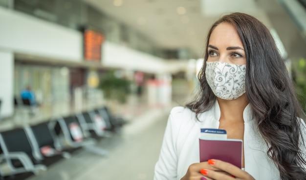 La viaggiatrice ansiosa tiene la carta d'imbarco e un passaporto in piedi in un terminal dell'aeroporto.