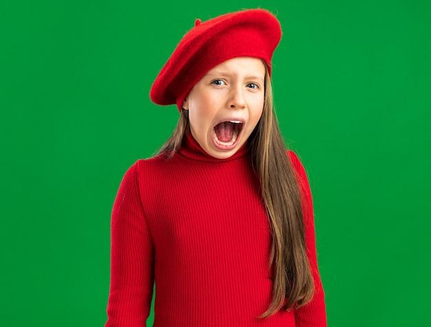 Ansiosa bambina bionda che indossa un berretto rosso che guarda la telecamera e urla isolata sulla parete verde con spazio per le copie
