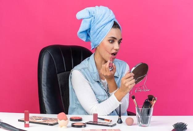 Donna abbastanza caucasica ansiosa con i capelli avvolti in un asciugamano seduto al tavolo con strumenti per il trucco che tengono e guardano lo specchio applicando il rossetto isolato sulla parete rosa con spazio di copia
