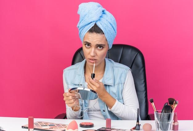 Donna abbastanza caucasica ansiosa con i capelli avvolti in un asciugamano seduto al tavolo con strumenti per il trucco che tengono specchio e lucidalabbra isolato sulla parete rosa con spazio di copia