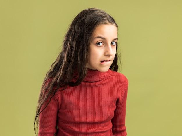 Adolescente ansioso che guarda il labbro mordente anteriore isolato sulla parete verde oliva con lo spazio della copia