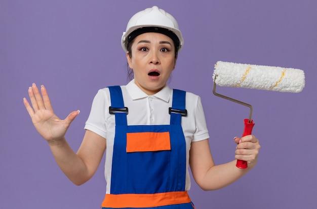 Ansiosa giovane ragazza asiatica del costruttore con il casco di sicurezza bianco che tiene il rullo di vernice