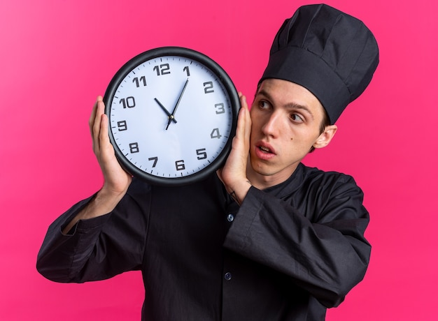 Ansioso giovane maschio biondo cuoco in uniforme da chef e cappello che tiene l'orologio guardandolo isolato su parete rosa