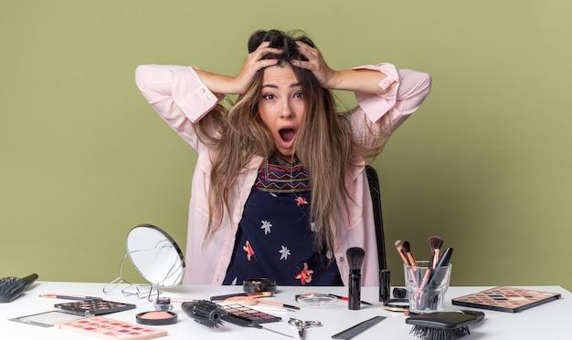 Ansiosa giovane ragazza bruna seduta al tavolo con strumenti per il trucco che tiene la testa isolata sul muro verde oliva con spazio copia