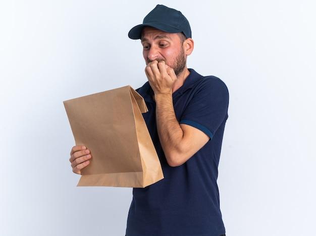 Ansioso giovane fattorino caucasico in uniforme blu e berretto che morde le dita tenendo e guardando il pacchetto di carta isolato sul muro bianco