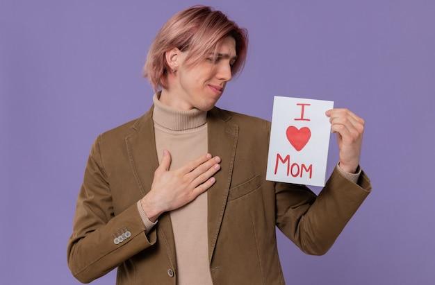 Ansioso giovane bell'uomo che tiene e guarda la lettera per sua mamma