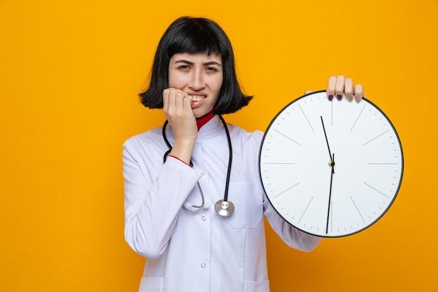 Ansiosa giovane bella ragazza caucasica in uniforme da medico con uno stetoscopio che tiene l'orologio e si morde le unghie