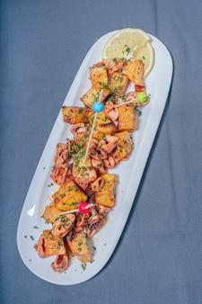Aperitivo o calamaretti tipici della tapa spagnola o chipirones con aglio e patate