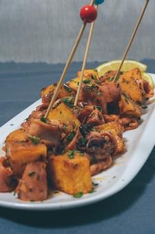 Aperitivo o calamaretti tipici della tapa spagnola con aglio e patate serviti su bianco allungato