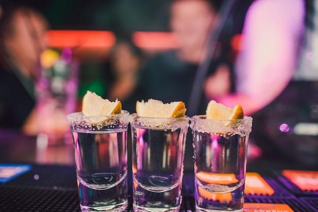 Aperitivo con gli amici al bar, cinque bicchieri di alcol con snack lime e pistacchio, sale e peperoncino per la decorazione. colpi di tequila, vodka, whisky, rum. messa a fuoco selettiva e copia spazio.