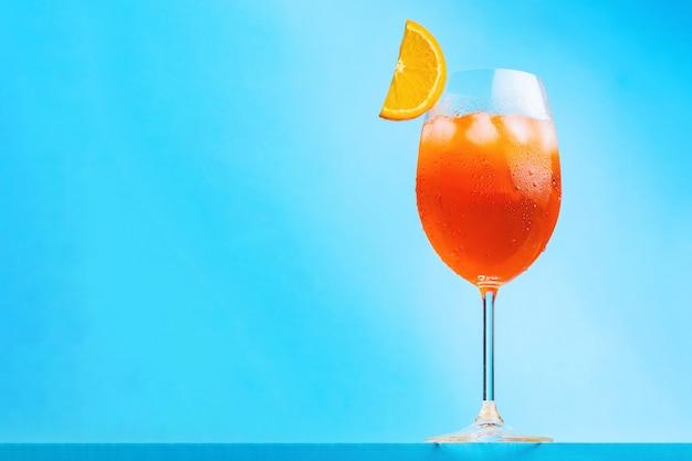 Aperol spritz cocktail su sfondo blu. bicchiere di cocktail aperol spritz con una fetta d'arancia. cocktail estivo italiano. orientamento orizzontale