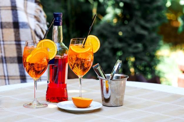 La tabella del plaid di vetro di cocktail dello spritz di aperol lascia la luce solare arancione dell'ombra del secchiello del ghiaccio del sole