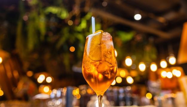 Aperol spritz cocktail in vetro sul tavolo di legno su sfondo scuro nella caffetteria.
