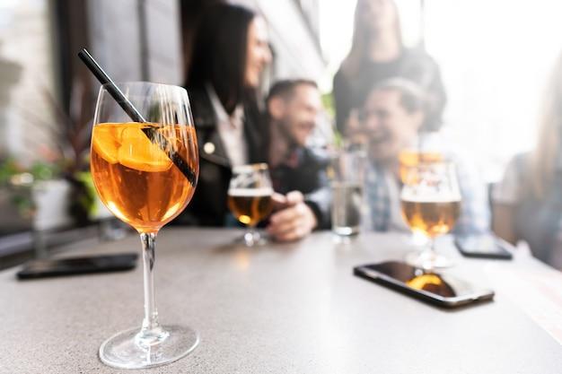 Aperol spritz cocktail su un tavolo con un gruppo di amici seduti