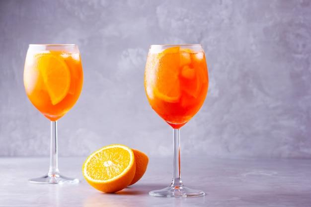 Aperol spritz cocktail. due bicchieri di aperol spritz con arancia tagliata. cocktail italiano estivo