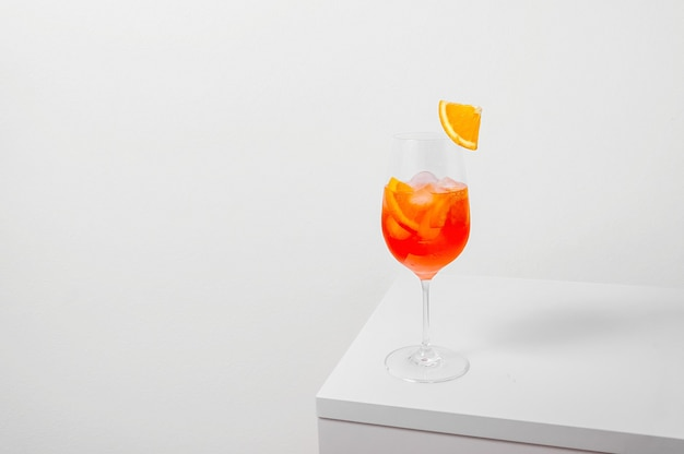 Aperol spritz cocktail nel bicchiere di vino con ghiaccio e fetta d'arancia su sfondo bianco