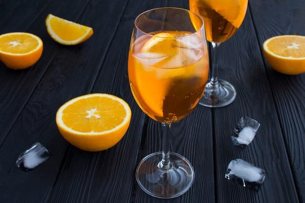 Aperol spritz cocktail in bicchieri di vino sulla tavola di legno nero. avvicinamento.