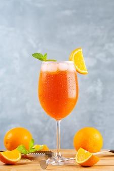 Aperol spritz cocktail con accessori da bar. cocktail italiano aperol spritz e un'arancia a fette su sfondo grigio. cocktail aperol spritz con menta fresca