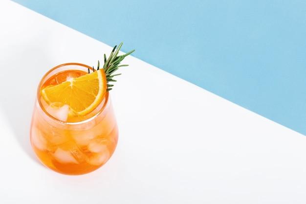 Aperol con ghiaccio in bicchieri su sfondo blu e bianco