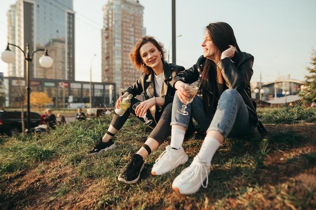 Aortrait di giovani ragazze felici in giacche di pelle che si siedono sull'erba