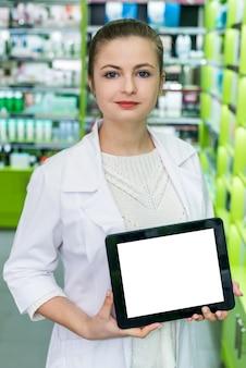 Apotecaria che mostra gadgett con schermo bianco in farmacia