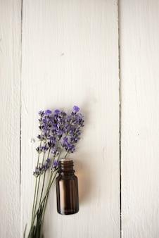 Olio di lavanda da farmacia con bouquet di fiori. lay piatto