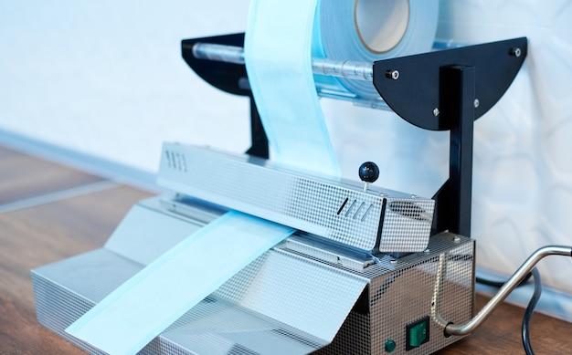 Apparecchio per sigillare strumenti medici in acciaio in confezioni sigillate separate per mantenere la sterilità prima dell'uso in studi dentistici e medici. attrezzature speciali per il confezionamento di dispositivi odontoiatrici.
