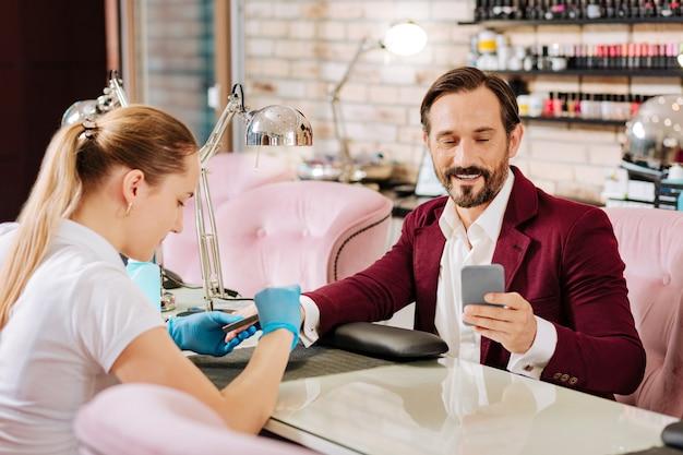Uomo maturo attraente che ottiene unghie fatte e che tiene il telefono