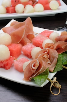 Antipasto di prosciutto cotto con melone e anguria e basilico su spiedino