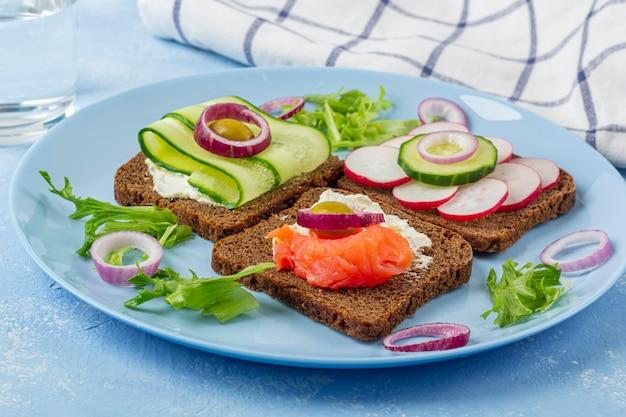 Antipasto, panino aperto con salmone su un piatto blu. cucina tradizionale italiana o scandinava. concetto di corretta alimentazione e alimentazione sana. avvicinamento