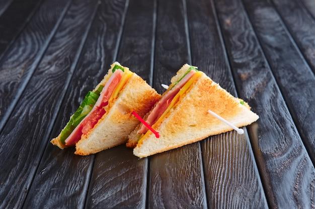 Antipasto per la ricezione. due mini club sandwich sul tavolo di legno