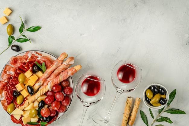Spuntini dell'antipasto messi con vino sulla superficie grigia
