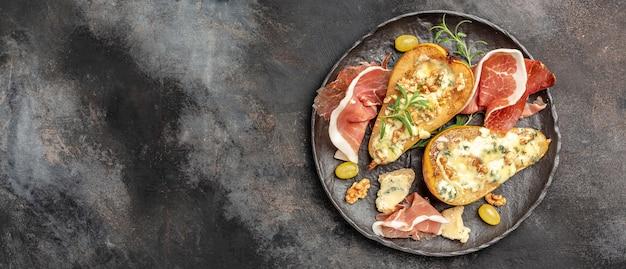 Antipasto di pere al forno con gorgonzola, noci e miele, prosciutto crudo. spuntini estivi. antipasto di pere con prosciutto, formato striscione lungo. vista dall'alto.