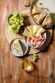 Antipasti antipasti con focaccia bianca siciliana. torta a fette di pane tradizionale con cipolla servita con prosciutto, formaggio, uva e bicchiere di vino bianco